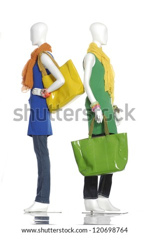 female clothing in jeans with scarf, bag on two mannequin back to back - stock photo