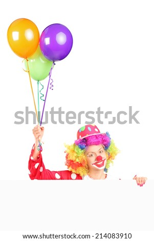 Female clown holding balloons behind a panel isolated on white background