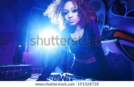 female club dj using turntable with headphones with lens flare - stock photo