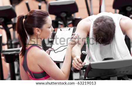 Female coach using a chronometer while man is pedaling on a bicycle in a fitness centre - stock photo