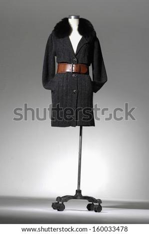female coat clothing on mannequin on light background  - stock photo