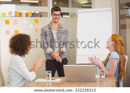 Female colleagues appreciating businessman of his presentation during meeting in office