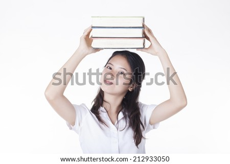 Female college student carrying a stack of book - stock photo