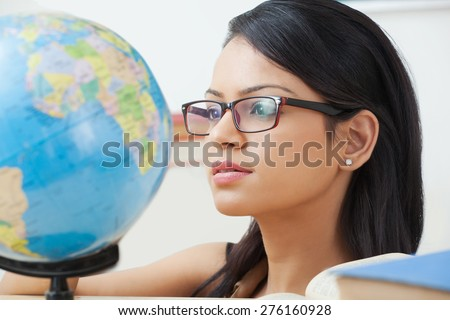 Female college student looking at a globe - stock photo