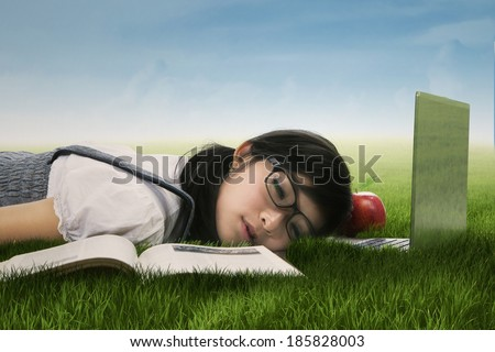 Female college student sleeping on the grass at campus