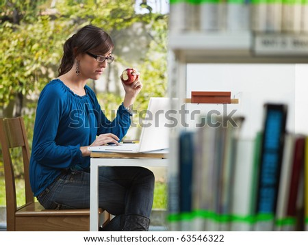 female college student studying in library and eating red apple. Horizontal shape, side view, three quarter length - stock photo