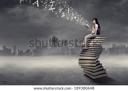 Female college student studying while sitting on a pile of books - stock photo