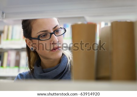 female college student taking book from shelf in library. Horizontal shape, front view, head and shoulders, copy space