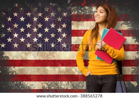 Female college student with books in park against usa flag in grunge effect - stock photo