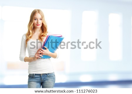 Female college student with folder standing in classroom