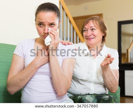 female comforts adult daughter   at home - stock photo