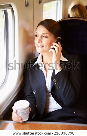 Female Commuter With Coffee On Train Using Mobile Phone - stock photo
