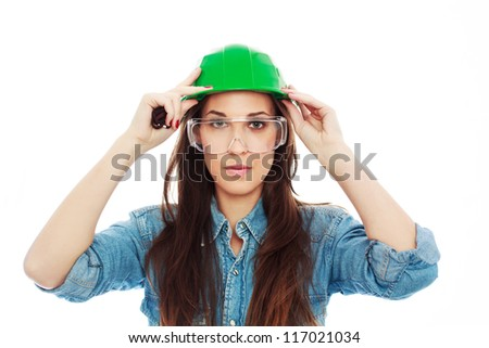 Female construction worker in safety glass holding green helmet - stock photo