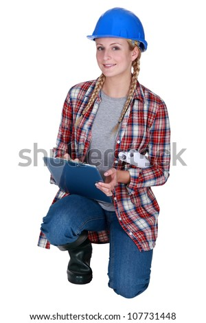 Female construction worker kneeling with clip-board - stock photo