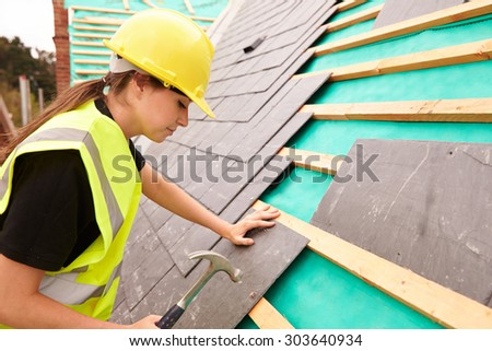 Female Construction Worker On Site Laying Slate Tiles - stock photo