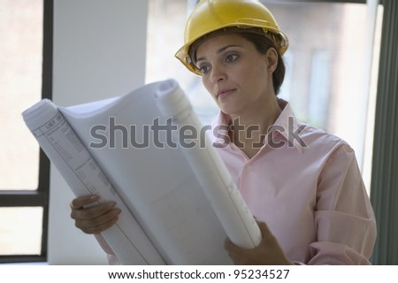 Female construction worker reading blue prints
