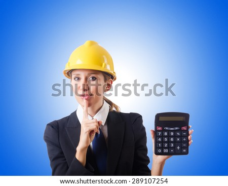 Female construction worker with calculator - stock photo