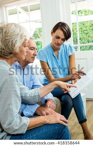 Female consultant reading report with senior couple at home - stock photo