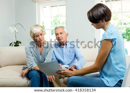Female consultant showing report to old couple while sitting on sofa at home