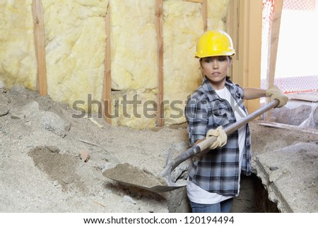 Female contractor digging sand at construction site - stock photo