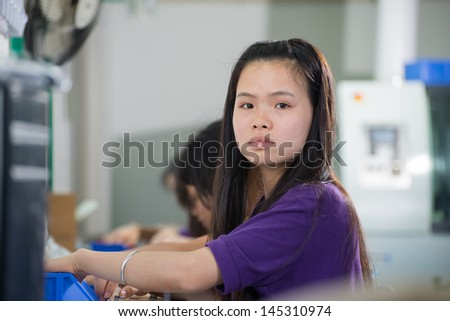 Female conveyor worker assembling electronic device on Chinese factory - stock photo