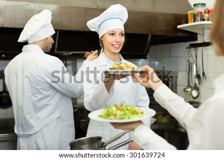 Female cook gives to charming waitress plates with prepared meal - stock photo