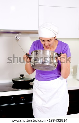 Female cook in a white apron and toque standing smelling her recipe in the pot which she has just removed from the hob - stock photo