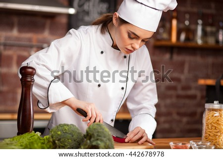 Female cook in a white hat in the kitchen. Female chef cutting pepper. Pasta, salad, broccoli, tomatoes and pepper on the table. - stock photo