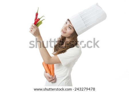female cook in white uniform with carrots and pepper - stock photo
