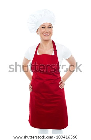 Female cook posing with hands on her waist in front of camera