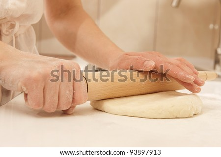 Female cook rolling dough with rolling-pin. Closeup view - stock photo