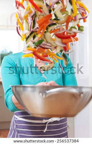 Female Cook Tossing Vegetables In Pan Obscuring Her Face - stock photo