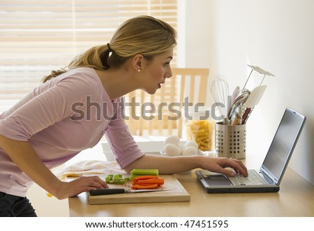 female cooking and looking up recipes on-line in kitchen - stock photo