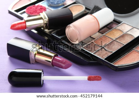 female cosmetic set on a purple wooden background