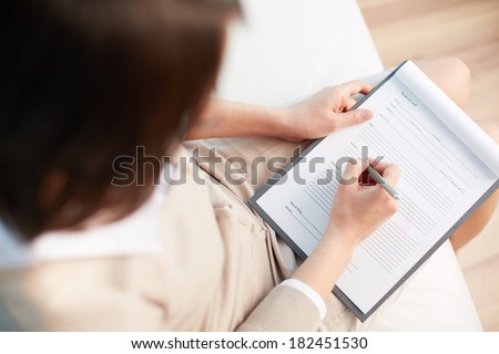 Female counselor writing down some information about her patient - stock photo