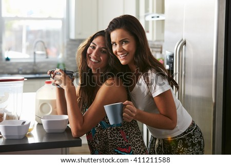 Female couple embracing in the kitchen look to camera - stock photo