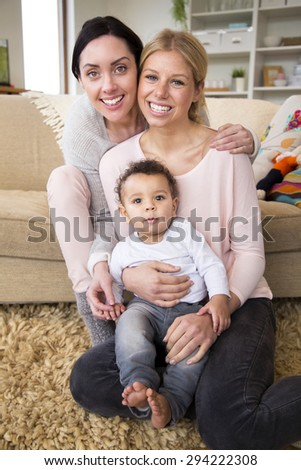 Female couple sit together with their son in their home and smile for the camera - stock photo
