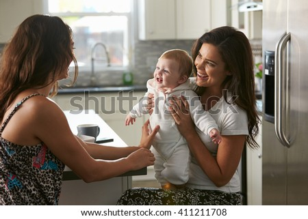 Female couple sitting in the kitchen holding their baby girl - stock photo
