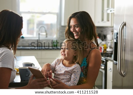 Female couple talking in the kitchen with their daughter