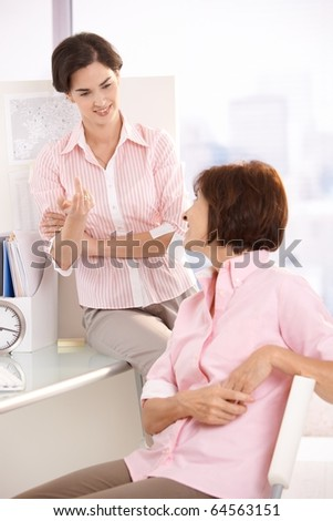 Female coworkers talking in bright office, smiling.