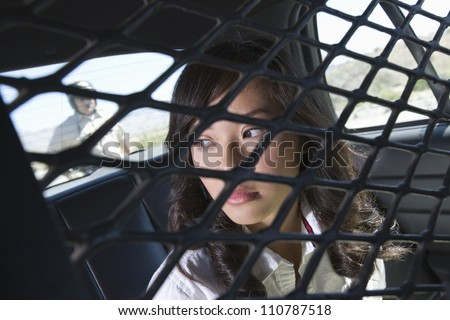 Female criminal sitting in police car with traffic cop in the background - stock photo