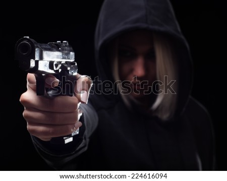 Female criminal wit the hood on her head shooting with gun on the street at night. - stock photo