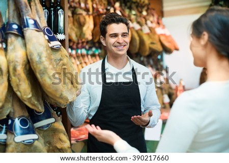 Female customer buying a Spanish jamon at a delicatessen store