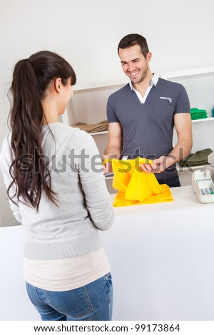 Female customer buying clothes at retail store - stock photo