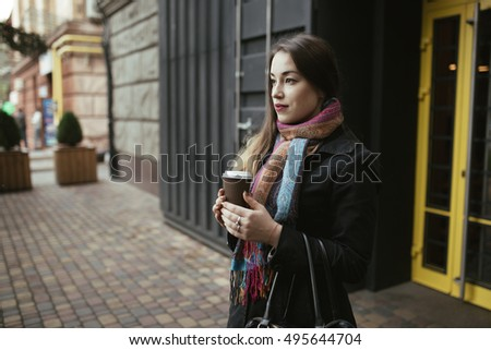 Female customer coming out from cafe with cup of coffee