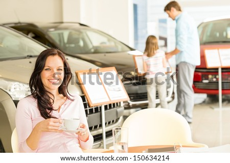 Female customer drinking coffee in car retail store - stock photo