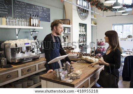 Female Customer Paying In Coffee Shop - stock photo