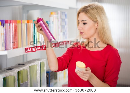 Female customer reading label on cosmetic bottle in supermarket - stock photo