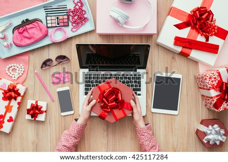 Female customer receiving a beautiful gift, she is shopping online using a laptop and a credit card, e-commerce and technology concept - stock photo