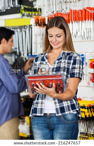 Female customer scanning pliers set through mobile phone with man in background at hardware store